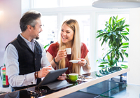 Businessman and woman laughing during coffee break in office 11015304534| 写真素材・ストックフォト・画像・イラスト素材|アマナイメージズ