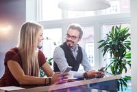 Businessman and woman chatting during coffee break in office 11015304536| 写真素材・ストックフォト・画像・イラスト素材|アマナイメージズ