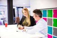 Businesswoman and man having brainstorming meeting in  office 11015304537| 写真素材・ストックフォト・画像・イラスト素材|アマナイメージズ