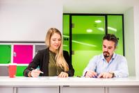 Businesswoman and man having brainstorming meeting in  office 11015304538| 写真素材・ストックフォト・画像・イラスト素材|アマナイメージズ