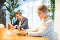 Businesswoman and man at office desk looking at digital tablet and smartphone 11015304540| 写真素材・ストックフォト・画像・イラスト素材|アマナイメージズ