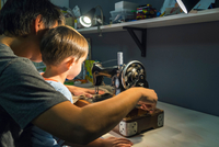 Over shoulder view of boy with father learning to turn sewing machine handle