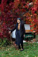 Portrait of senior woman with walking stick standing in autumn garden