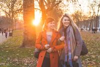 Two female friends walking through park, sunset 11015304667| 写真素材・ストックフォト・画像・イラスト素材|アマナイメージズ