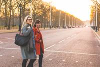 Two female friends crossing road, smiling 11015304670| 写真素材・ストックフォト・画像・イラスト素材|アマナイメージズ