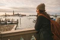 Woman on bridge in Grand Canal, San Giorgio Maggiore Island in background, Venice, Italy