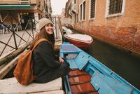 Woman sitting by canal, Venice, Italy 11015304804| 写真素材・ストックフォト・画像・イラスト素材|アマナイメージズ