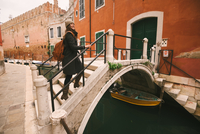 Woman crossing bridge over canal, Venice, Italy