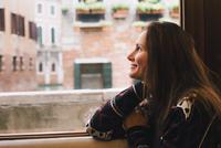 Woman looking out window, Venice, Italy 11015304808| 写真素材・ストックフォト・画像・イラスト素材|アマナイメージズ