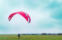 Male parachutist landing on airfield
