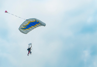 View of tandem parachuting down against cloudy sky
