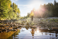 Female hiker walking on riverbed in Englishman River Falls Provincial Park , Vancouver Island, British Columbia, Canada