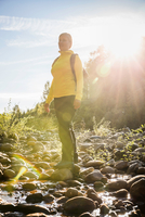 Female hiker gazing from sunlit riverbed in Englishman River Falls Provincial Park , Vancouver Island, British Columbia, Canada