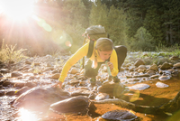 Female hiker drinking river water using water filter  in Englishman River Falls Provincial Park , Vancouver Island, British Colu