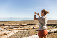 Woman photographing in Miracle Beach Provincial Park, Vancouver Island, British Columbia, Canada