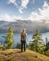 Female hiker looking out over Comox Lake, Coutenay, Vancouver Island, British Columbia, Canada