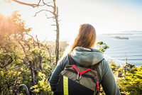Female hiker looking out from coastal forest, Pacific Rim National Park, Vancouver Island, British Columbia, Canada