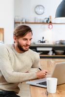 Mid adult man looking at laptop on table 11015305009  写真素材・ストックフォト・画像・イラスト素材 アマナイメージズ