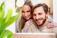 Mid adult couple looking at laptop together in kitchen