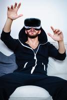 Mid adult man on sofa with arms raised watching virtual reality headset 11015305020| 写真素材・ストックフォト・画像・イラスト素材|アマナイメージズ