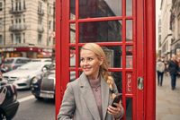 Mid adult woman standing in front of telephone box, holding smartphone 11015305197| 写真素材・ストックフォト・画像・イラスト素材|アマナイメージズ