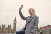Mid adult woman taking selfie, using smartphone, Houses of Parliament in background, London, England 11015305199| 写真素材・ストックフォト・画像・イラスト素材|アマナイメージズ