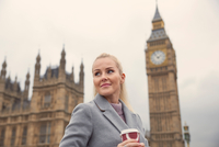Portrait of mid adult woman holding coffee cup, Houses of Parliament in background, London, England 11015305200| 写真素材・ストックフォト・画像・イラスト素材|アマナイメージズ