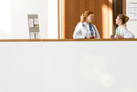 Two young female doctors leaning against hospital balcony talking 11015305322| 写真素材・ストックフォト・画像・イラスト素材|アマナイメージズ