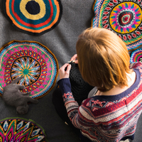 Overhead view of woman sitting on floor crocheting, surrounded by crochet circles 11015305371| 写真素材・ストックフォト・画像・イラスト素材|アマナイメージズ