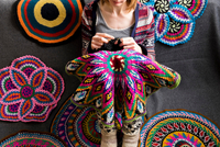 Cropped view of woman sitting on floor crocheting, surrounded by crochet circles 11015305372| 写真素材・ストックフォト・画像・イラスト素材|アマナイメージズ