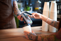 Customer paying for her coffee by mobile payment 11015305470| 写真素材・ストックフォト・画像・イラスト素材|アマナイメージズ