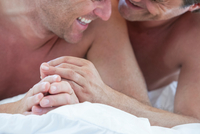 Cropped shot of happy male couple on bed