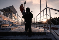 Boy carrying snowboard up steps 11015305923| 写真素材・ストックフォト・画像・イラスト素材|アマナイメージズ