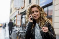 Woman in street making telephone call on mobile phone 11015306090| 写真素材・ストックフォト・画像・イラスト素材|アマナイメージズ