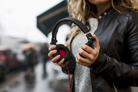 Woman in street holding headphones