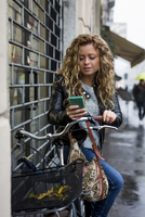 Woman with bicycle in street looking at smartphone