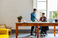 Male couple working at home together, at desk, sharing ideas 11015306171| 写真素材・ストックフォト・画像・イラスト素材|アマナイメージズ