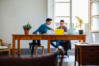 Male couple working at home together, sitting at desk,  looking at documents 11015306175| 写真素材・ストックフォト・画像・イラスト素材|アマナイメージズ