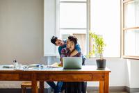 Male couple at home, man sitting at table using laptop, partner hugging him 11015306178| 写真素材・ストックフォト・画像・イラスト素材|アマナイメージズ