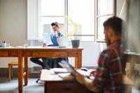 Male couple at home, man sitting at table reading document, partner looking through magazine 11015306179| 写真素材・ストックフォト・画像・イラスト素材|アマナイメージズ