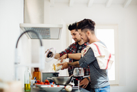 Male couple preparing meal together in kitchen