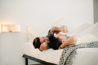 Male couple relaxing in bed, holding hands