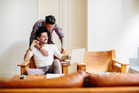 Young man at home, sitting in chair, using laptop, his partner hugging him from behind 11015306231| 写真素材・ストックフォト・画像・イラスト素材|アマナイメージズ