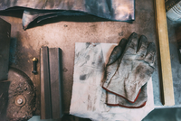Overhead view of metals and protective gloves on forge workbench 11015306319| 写真素材・ストックフォト・画像・イラスト素材|アマナイメージズ