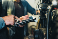 Two mature men, working in garage, using digital tablet, close-up 11015306399  写真素材・ストックフォト・画像・イラスト素材 アマナイメージズ