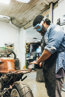 Mature man, working on motorcycle in garage 11015306400| 写真素材・ストックフォト・画像・イラスト素材|アマナイメージズ