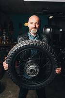 Portrait of mature man, in garage, holding motorcycle tire 11015306410| 写真素材・ストックフォト・画像・イラスト素材|アマナイメージズ