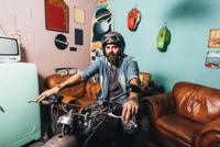 Portrait of mature man indoors, sitting on motorcycle 11015306411| 写真素材・ストックフォト・画像・イラスト素材|アマナイメージズ