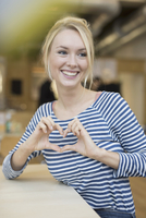 Young woman making heart hands in cafe 11015306595| 写真素材・ストックフォト・画像・イラスト素材|アマナイメージズ