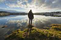 Man standing at water's edge, looking at view, rear view, Tjarnarholl, Iceland 11015306934| 写真素材・ストックフォト・画像・イラスト素材|アマナイメージズ